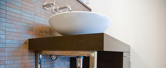A wash basin in a teenage boys' en-suite bathroom, using wenge dark wood cabinetry to compliment the earthy metallic mosaic tiles.